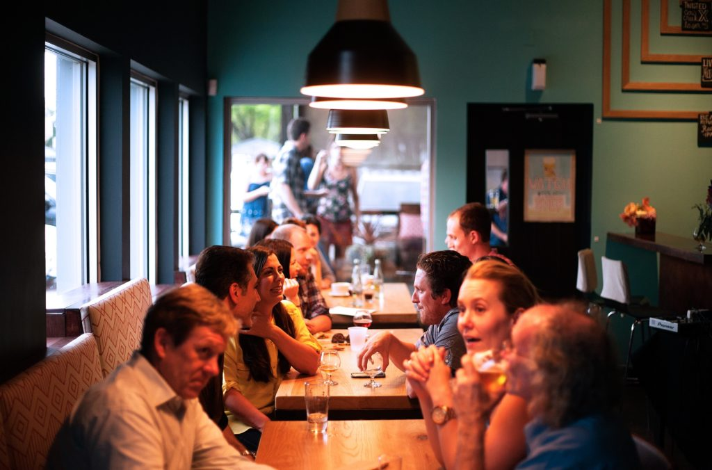 Groups of people conversing in a restaurant.