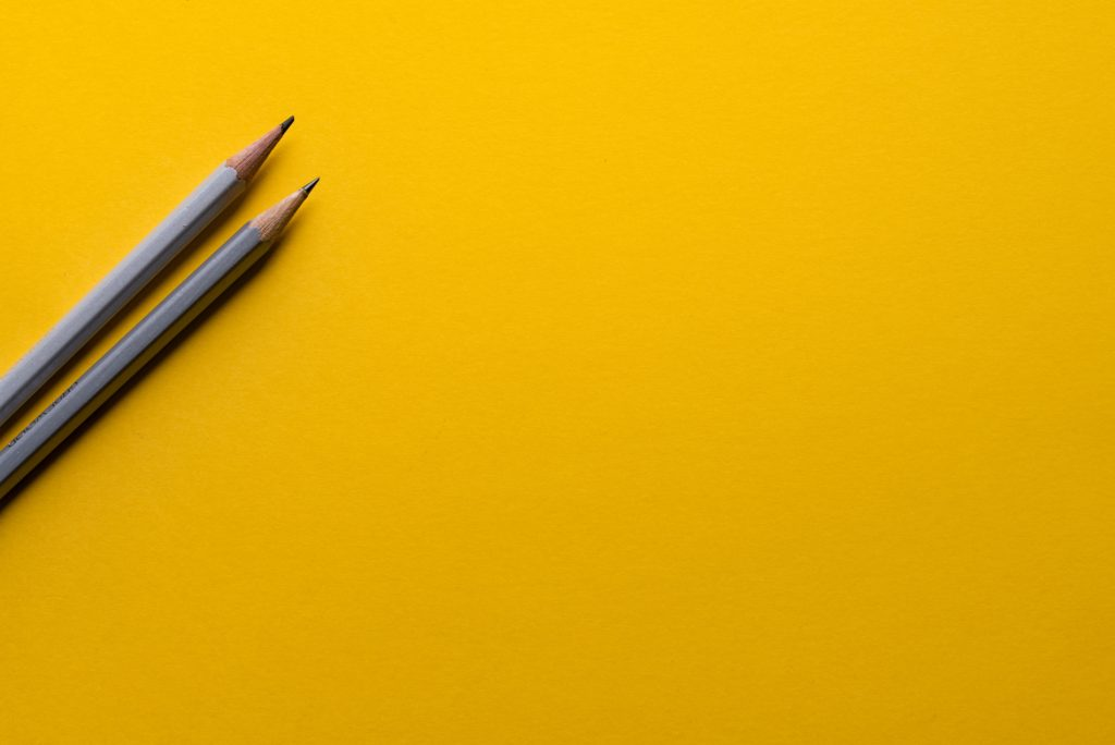 Yellow background with two pencils.